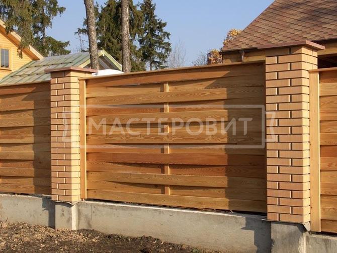 Плетеный забор из дерева с кирпичными столбами