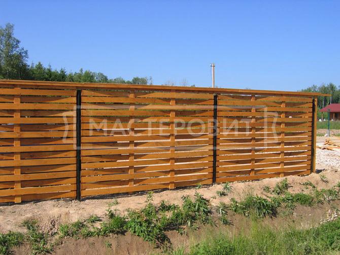 Плетеный забор из дерева с металлическими столбами